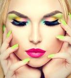 Γυναίκα ομορφιάς με το ζωηρό makeup και τη ζωηρόχρωμη στιλβωτική ουσία καρφιών Στοκ Φωτογραφία