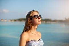 Γυναίκα ομορφιάς παραλιών wellness SPA στη swimwear χαλάρωση μπικινιών και το λούσιμο ήλιων κοντά στην μπλε λιμνοθάλασσα Όμορφες  στοκ φωτογραφία