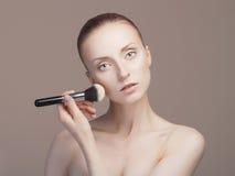 γυναίκα ομορφιάς που εφαρμόζει τη σύνθεση Στοκ Εικόνα