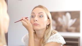 Γυναίκα ομορφιάς που ισχύει makeup όμορφο κορίτσι που φαίνεται καθρέφτης φιλμ μικρού μήκους