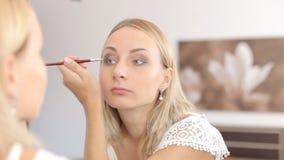 Γυναίκα ομορφιάς που ισχύει makeup όμορφο κορίτσι που φαίνεται καθρέφτης απόθεμα βίντεο