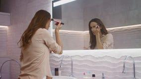 Γυναίκα ομορφιάς που κάνει makeup στο λουτρό Ευτυχής γυναίκα που κάνει το πρωί makeup απόθεμα βίντεο