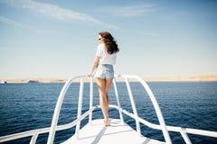 Γυναίκα ομορφιάς που στέκεται στη μύτη γιοτ στο υπόβαθρο θάλασσας Στοκ Φωτογραφία