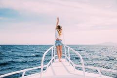 Γυναίκα ομορφιάς που στέκεται στη μύτη γιοτ στο υπόβαθρο θάλασσας Στοκ Φωτογραφίες