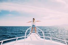 Γυναίκα ομορφιάς που στέκεται στη μύτη γιοτ στο υπόβαθρο θάλασσας Στοκ Εικόνα