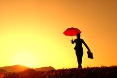 γυναίκα ομπρελών ηλιοβασιλέματος επιχειρησιακών σκιαγραφιών Στοκ Φωτογραφίες