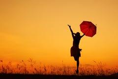 γυναίκα ομπρελών ηλιοβασιλέματος σκιαγραφιών άλματος Στοκ Εικόνες
