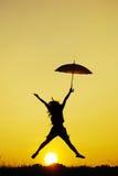 γυναίκα ομπρελών ηλιοβασιλέματος σκιαγραφιών άλματος Στοκ Φωτογραφίες