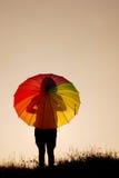 γυναίκα ομπρελών ηλιοβασιλέματος σκιαγραφιών άλματος Στοκ εικόνα με δικαίωμα ελεύθερης χρήσης