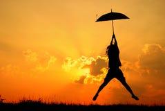 γυναίκα ομπρελών ηλιοβασιλέματος σκιαγραφιών άλματος Στοκ φωτογραφία με δικαίωμα ελεύθερης χρήσης
