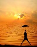 γυναίκα ομπρελών ηλιοβασιλέματος σκιαγραφιών λιμνών άλματος Στοκ Εικόνες