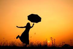 γυναίκα ομπρελών ηλιοβασιλέματος σκιαγραφιών Στοκ Εικόνες