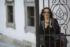 γυναίκα πίσω από τον εκλεκτής ποιότητας φράκτη σιδήρου στην παλαιά πόλη Στοκ Φωτογραφίες