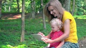 Γυναίκα παραμανών με το χαριτωμένο κοριτσάκι που χρησιμοποιεί τον υπολογιστή ταμπλετών στο πάρκο απόθεμα βίντεο