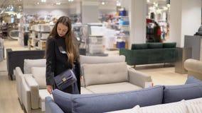Γυναίκα πελατών που αγοράζει τα νέα έπιπλα - καναπές ή καναπές σε ένα κατάστημα απόθεμα βίντεο