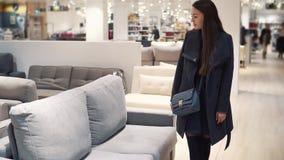 Γυναίκα πελατών που αγοράζει τα νέα έπιπλα - καναπές ή καναπές σε ένα κατάστημα φιλμ μικρού μήκους