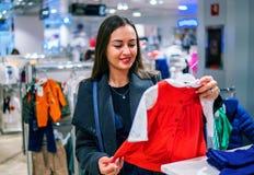 Γυναίκα πελατών που επιλέγει τα ενδύματα μωρών στο κατάστημα στοκ φωτογραφία με δικαίωμα ελεύθερης χρήσης