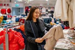 Γυναίκα πελατών που επιλέγει τα ενδύματα μωρών στο κατάστημα στοκ φωτογραφίες