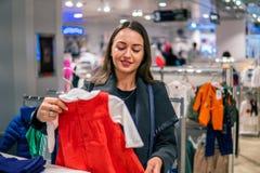 Γυναίκα πελατών που επιλέγει τα ενδύματα μωρών στο κατάστημα στοκ εικόνα