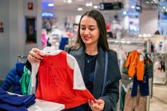 Γυναίκα πελατών που επιλέγει τα ενδύματα μωρών στο κατάστημα στοκ φωτογραφίες με δικαίωμα ελεύθερης χρήσης