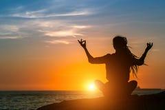 Γυναίκα περισυλλογής στην ωκεάνια ακτή κατά τη διάρκεια του καταπληκτικού ηλιοβασιλέματος Στοκ εικόνα με δικαίωμα ελεύθερης χρήσης