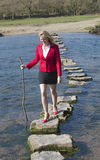 Γυναίκα περπατώντας πετρών που περπατά πέρα από τον ποταμό Στοκ φωτογραφία με δικαίωμα ελεύθερης χρήσης