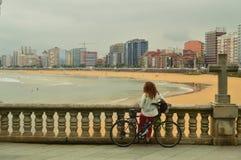 Γυναίκα ποδηλατών που απολαμβάνει τα τοπία του κόλπου με έναν σταυρό εκτός από την στην παραλία του SAN Lorenzo Gijon Ταξίδι, δια στοκ φωτογραφίες με δικαίωμα ελεύθερης χρήσης