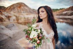 Γυναίκα πορτρέτου με τα μπλε μάτια και την ανθοδέσμη των λουλουδιών στα χέρια της στη φύση Πανέμορφη τρίχα και τέλειο δέρμα Στοκ φωτογραφία με δικαίωμα ελεύθερης χρήσης