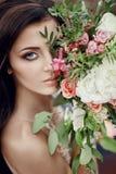Γυναίκα πορτρέτου με τα μπλε μάτια και την ανθοδέσμη των λουλουδιών στα χέρια της στη φύση Πανέμορφη τρίχα και τέλειο δέρμα Στοκ Εικόνες