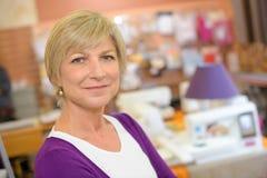 Γυναίκα πορτρέτου με το κατάστημα εγχώριων διακοσμήσεων στο υπόβαθρο στοκ φωτογραφία
