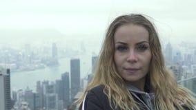Γυναίκα πορτρέτου που κοιτάζει στη κάμερα ενώ πανόραμα πόλεων Χονγκ Κονγκ ταξιδιού από μέγιστη Βικτώρια Ευρωπαία γυναίκα τουριστώ απόθεμα βίντεο