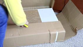 Γυναίκα που ένα κουτί από χαρτόνι με τα νέα έπιπλα με το μαχαίρι κατασκευής ή γραφείων - που κινείται προς το καινούργιο σπίτι κα φιλμ μικρού μήκους