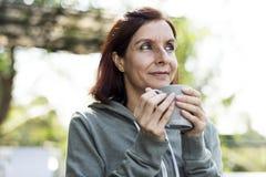 Γυναίκα που έχει μια κούπα του καφέ Στοκ εικόνες με δικαίωμα ελεύθερης χρήσης