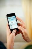 Γυναίκα που έχει πρόσβαση στον ιστοχώρο πειραχτηριών στο iPhone 4 της Apple Στοκ Εικόνες