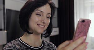 Γυναίκα που έχει την τηλεοπτική συνομιλία που χρησιμοποιεί την απόλαυση smartphone που κουβεντιάζει στο φίλο απόθεμα βίντεο