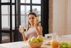 Γυναίκα που έχει την υγιεινή διατροφή που τρώει το μήλο και το πόσιμο γάλα στοκ φωτογραφία