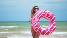 Γυναίκα που έχει τη διασκέδαση και το χαμόγελο που χορεύουν με ρόδινο doughnut κορίτσι στο bicini που φορά τα γυαλιά ηλίου στην π φιλμ μικρού μήκους