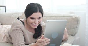 Γυναίκα που έχει τη διασκέδαση που χρησιμοποιεί την ψηφιακή ταμπλέτα στον καναπέ φιλμ μικρού μήκους