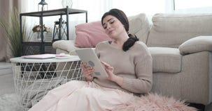 Γυναίκα που έχει τη διασκέδαση που χρησιμοποιεί την ψηφιακή ταμπλέτα στο σπίτι φιλμ μικρού μήκους