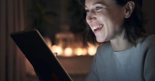 Γυναίκα που έχει τη διασκέδαση που χρησιμοποιεί την ψηφιακή ταμπλέτα τη νύχτα απόθεμα βίντεο