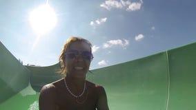 Γυναίκα που έχει τη διασκέδαση, που γλιστρά στο πάρκο νερού φιλμ μικρού μήκους