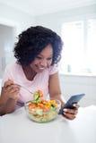 Γυναίκα που έχει τη σαλάτα χρησιμοποιώντας το κινητό τηλέφωνο Στοκ φωτογραφίες με δικαίωμα ελεύθερης χρήσης