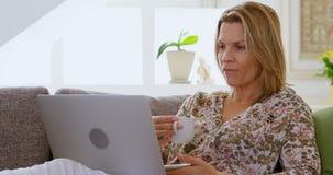 Γυναίκα που έχει τον καφέ χρησιμοποιώντας το lap-top στον καναπέ 4k απόθεμα βίντεο
