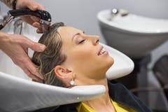 Γυναίκα που έχει το κεφάλι της πλυμένο από τον κομμωτή Στοκ Εικόνες