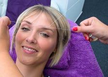 Γυναίκα που έχει το πέρασμα κλωστής σε βελόνα της διαδικασίας αφαίρεσης τρίχας Στοκ Φωτογραφία