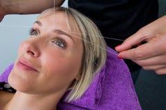 Γυναίκα που έχει το πέρασμα κλωστής σε βελόνα της διαδικασίας αφαίρεσης τρίχας Στοκ Εικόνα