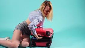 Γυναίκα που έχει το πρόβλημα με το κλείσιμο της βαλίτσας απόθεμα βίντεο