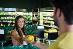 Γυναίκα που δίνει τα φρούτα στον ταμία για την τιμολόγηση στην υπεραγορά στοκ φωτογραφίες