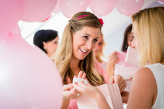 Γυναίκα που δίνει το δώρο στον έγκυο φίλο στο ντους μωρών Στοκ φωτογραφία με δικαίωμα ελεύθερης χρήσης