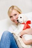 Γυναίκα που αγκαλιάζει το άσπρο κουτάβι με την κόκκινη κορδέλλα Στοκ Φωτογραφία